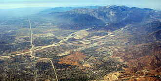 Transverse Ranges - View looking westward at the western portion of the San Bernardino and San Gabriel Mountains, with the San Bernardino Valley to the left, with San Bernardino itself in the foreground. The Foothill Freeway (I-210) runs toward the horizon, while I-15 runs through Cajon Pass to the right.
