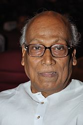 A photograph of an old man wearing white kurta and glasses.