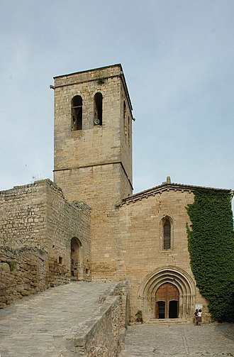 Guimerà - Santa Maria de Guimerà parish church, with at left, one of the town wall's gates.