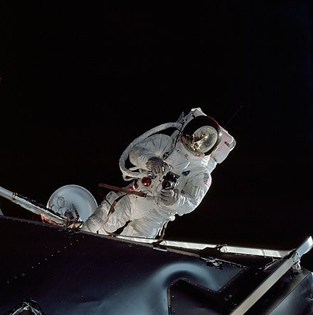 Schweickart during his EVA, photographed by Scott standing up in the command module hatch