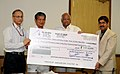 Sharad Pawar being presented a dividend cheque by the Chairman and Managing Director of State Farms Corporation of India, Shri V.K. Gaur, in New Delhi. The Minister of State for Agriculture.jpg
