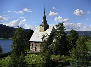 A little stone church with a little steeple on a wooden belfry sits in a green graveyard overlooking a lake and mountains.
