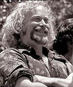 Black and white photo of a man in his fifties, looking to the right, smiling and folding his arms at his chest.  He has curly, light-colored hair and a goatee, and is wearing a flower-patterned shirt with rolled-up sleeves.
