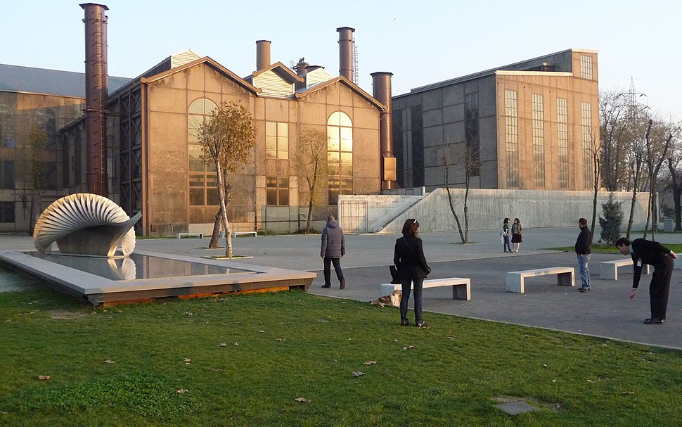 A brick factory stands in front of a park, with open green space, a reflecting pool, and benches