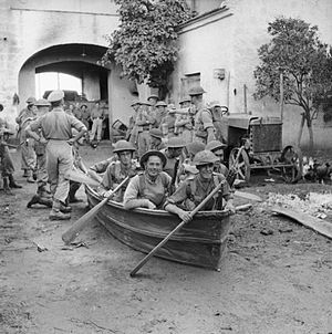 131st Infantry Brigade (United Kingdom) - An infantry section from 'B' Company of the 1/6th Battalion, Queen's Royal Regiment try out their collapsible boats in a farmyard in preparation for crossing the Volturno river, Italy, 8 October 1943.