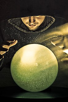 Colour photograph of a hooded wizard gazing into a green crystal ball with the ghost image of his face floating to the right.