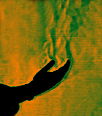 Convective heat transfer - This colour schlieren image reveals thermal convection from a human hand (in silhouette form) to the surrounding still exchange.