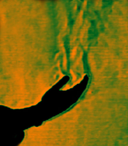 This color schlieren image reveals thermal convection from a human hand (in silhouette) to the surrounding still atmosphere. Thermal-plume-from-human-hand.jpg