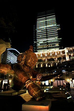 The sculpture lit up at night with a skyscraper behind it