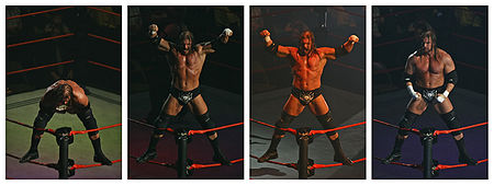 Triple H performing his iconic ring entrance pose, mounting the second rope and displaying his muscularity with the arena darkened and strobing colored lights