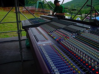 Sound reinforcement system - A Yamaha PM4000 and a Midas Heritage 3000 mixing console at the Front of House position at an outdoor concert.