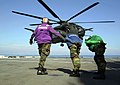 "US Navy 020909-N-0111R-004 Three flight deck crew members brace against the rotor wash of a MH-53E ""Sea Dragon"".jpg"