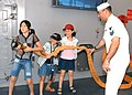 US Navy 050807-N-9860Y-101 Electronics Technician 1st Class Tyrone A. Gideon of Emmett, Idaho, shows Japanese children the proper way to handle a fire hose as they tour the main deck of USS Blue Ridge (LCC 19).jpg