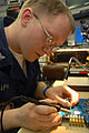 US Navy 070129-N-3038W-073 Electronics Technician 3rd Class Christopher Ralph makes repairs with a soldering iron on a circuit board in the micro-miniature electronics repair shop.jpg