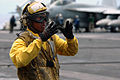 US Navy 070804-N-7883G-060 Aviation Boatswain's Mate (Handling) Airman Johnkeith Elopre, directs aircraft during flight operations aboard USS Kitty Hawk (CV 63).jpg