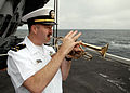 US Navy 070819-N-7981E-122 Chief Warrant Officer 3 Rob Holland plays taps at the completion of a burial at sea ceremony aboard Nimitz-class aircraft carrier USS Abraham Lincoln (CVN 72).jpg