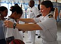 US Navy 090126-N-2013O-052 Lt. j.g. Kristina Rohlin, from Russell, Pa., assigned to the Arleigh Burke-class guided-missile destroyer USS Lassen (DDG 82), checks the size of a shirt before giving it to a girl at the Missionary D.jpg