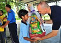 US Navy 100609-N-7643B-073 Lt. Mark Hughes, chaplain for Destroyer Squadron (DESRON) 31, presents a gift basket to a girl from the Rumah Wawasan Children's Home.jpg