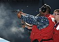 US Navy 100618-N-6632S-301 Aviation Ordnanceman 1st Class Archie L. Gittens fires a pistol for small arms qualification.jpg