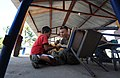 US Navy 110128-N-7589W-405 Cpl. Paul Fuit, assigned to 2nd Marine Logistics Group, shows a child how to use a rasp to smooth wood desks at Escuela.jpg