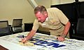 US Navy 110809-N-HC601-018 Rear Adm. Glenn Robillard, commander of Navy Exchange Services Command, signs a commemorative Fleet and Industrial Supp.jpg