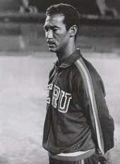 Photo of a man with a moustache, wearing a sports outfit, in a thoughtful pose