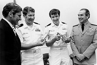 "Duke Cunningham - June 1972 – Lieutenant Cunningham (second from left) in a ceremony honoring him and Lieutenant (JG) William P. Driscoll (third from left), the Navy's only Vietnam War air ""Aces"". On the left is John Warner, then Secretary of the Navy, and on the right is Admiral Elmo Zumwalt, then Chief of Naval Operations."