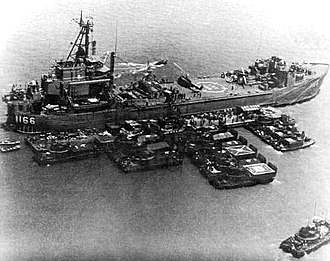 USS Washtenaw County (LST-1166) - USS Washtenaw County (LST-1166) in the Mekong Delta, circa 1968. Two helicopters sit atop her flight deck.