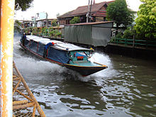 A boat, about mười mét (33 foot) long, travelling along a canal, the dark water breaking up in foam as it passes
