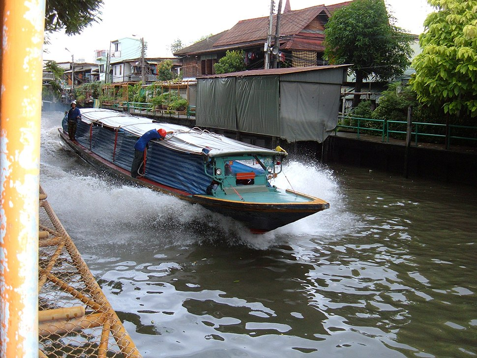 A boat, about ten metres (33 feet) long, travelling along a canal, the dark water breaking up in foam as it passes