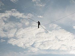 A man walks across a tightrope, with only a clouded sky in the background