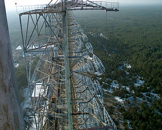 Duga radar - Duga-1 array within the Chernobyl Exclusion Zone. The array of pairs of cylindrical/conical cages on the right are the driven elements, fed at the facing points with a form of ladder line suspended from stand-off platforms at top right. A backplane axel reflector of small wires can just be seen left of center, most clearly at the bottom of the image.