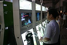 A man and other gamers play Project Sylpheed, which is running on a line of four upright cabinets that each holds an Xbox 360 game console and a LCD display.