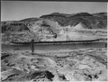 """East side excavation area in the foreground showing feeder belts to cross-river conveyor, cofferdam in distance."" - NARA - 293963.tif"