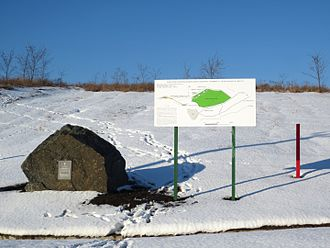 Khotiv hillfort - Khotiv hillfort. A stone with a metallic plaque, an information board and one of the red pillars which mark the reduced area of the archaeological monument (2016 version, shown in green on the board).