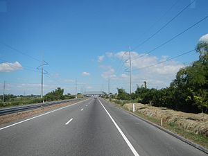 Subic–Clark–Tarlac Expressway - A portion of SCTEX near Concepcion, Tarlac. The Concepcion-Clark transmission line of National Grid Corporation of the Philippines can be seen on both sides of the highway.