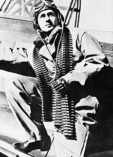 Three-quarter portrait of moustachioed man in flying suit with a belt of machine-gun ammunition slung over his shoulders, leaning against an aeroplane
