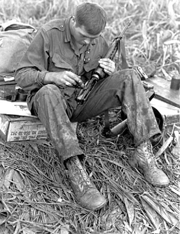 U.S. Soldier cleans his XM16E1 during the Viet...