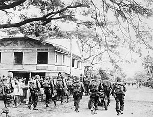 11th Airborne Division (United States) - Troops of the 188th Glider Infantry Regiment make their way through the town of Nasugbu on the island of Luzon, 31 January 1945.