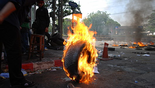A burning tire is about to be rolled to create a smoke-screen during the 2010 Thai unrest.