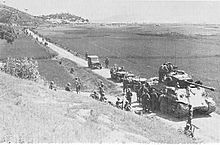 A column to soldiers and vehicles move down a river