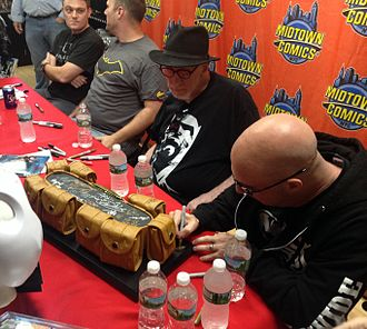 Batman's utility belt - Artist Greg Capullo signs a replica Batman utility belt during an appearance at Midtown Comics in Manhattan. Beside him from left to right are fellow Batman creators Scott Snyder, Tom King, and Frank Miller.