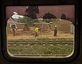 A man rides a bicycle along a footpath parallel to train tracks in Kampala.jpg