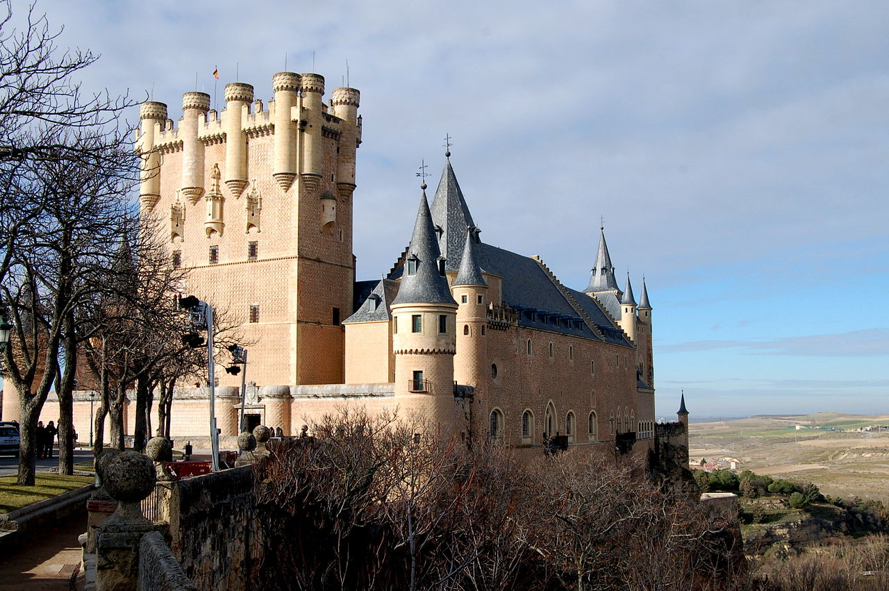 A castle high on a rocky peninsula above a plain. It is dominated by a tall rectangular tower rising above a main building with steep slate roof. The walls are pink, and covered with a sculptural pattern. There is a variety of turrets and details.