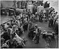 American soldiers, hardened and ready, lounge under full fighting equipment on the deck of a Coast Guard assault... - NARA - 196237.jpg