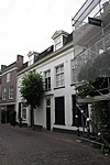 foto van Huis met gepleisterde kroonlijstgevel en voordeur met zijpilasters en bekroning