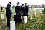 Barack Obama leaves a presidential coin at the gravesite of Ross McGinnis at Arlington Cemetery