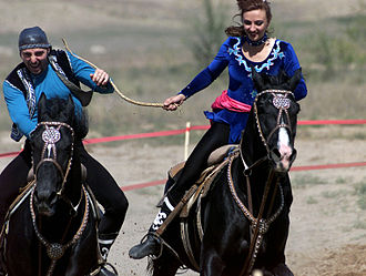 """Kyz kuu - Riders in traditional Kazakh dress play Kyz kuu.  In the depiction, the young woman is """"winning"""" by whipping the young man."""