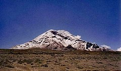 A snow-capped mountain lies in the distance against a cloudless blue sky. The land in the foreground is very barren.