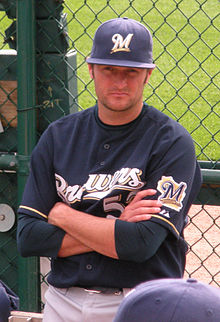 "A man wearing gray pants, a navy blue baseball jersey with ""Brewers"" written across the chest in white and gold letters, and a navy blue cap stands with his arms crossed"